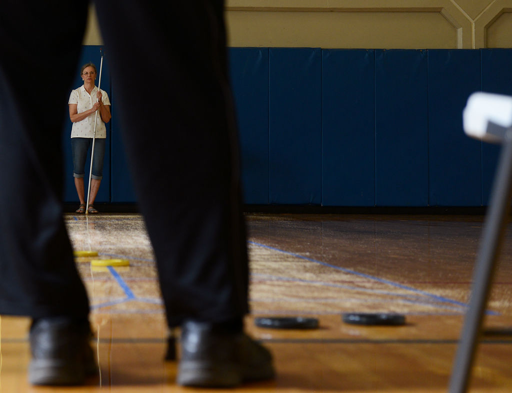 Rita Eckert watches her shot land during the Senior Games shuffleboard competition