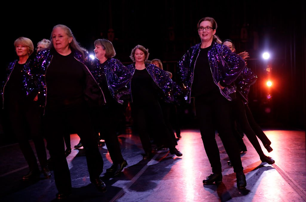 A group of older adult dancers perform a tap dance routine