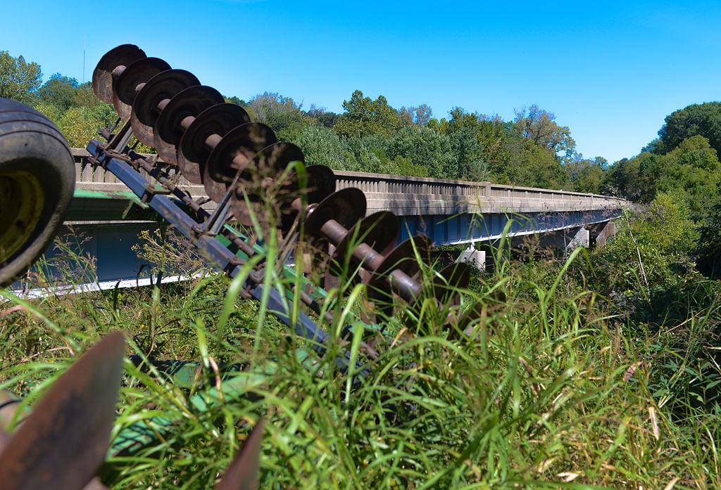 Abandoned farm equipment sits in unkempt vegetation at the Route 40 Bridge