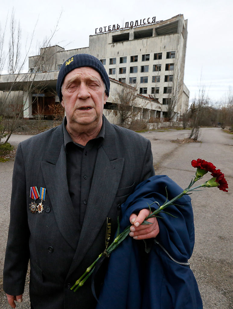Former resident of Pripyat, Olexander Zabelchenko holds flowers
