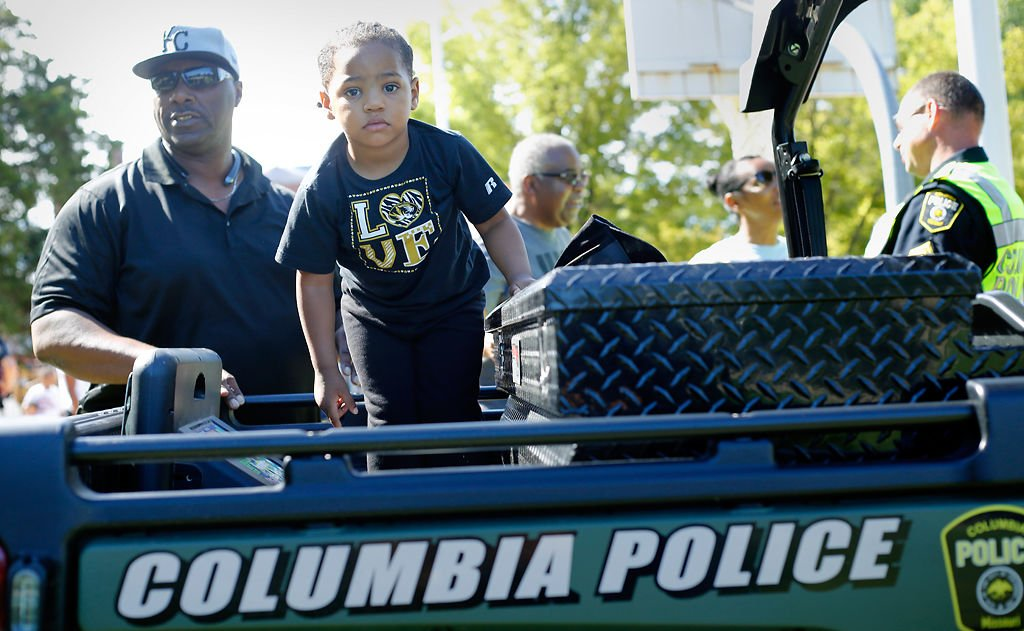 Liam Cobbins climbs in the back of a police cart