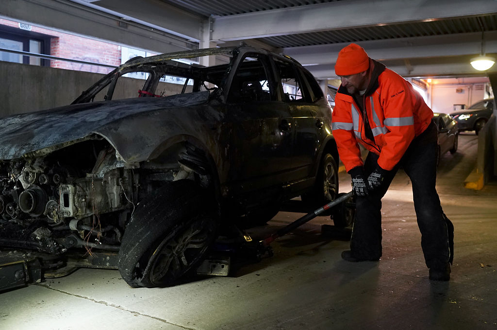 Michael Hartman lifts the front end of a BMW X3 that caught on fire