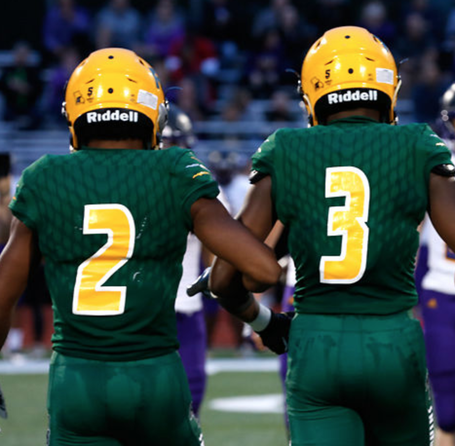 Rock Bridge football captains Nathaniel Peat and Martez Manuel  link arms as they walk to midfield for the coin toss