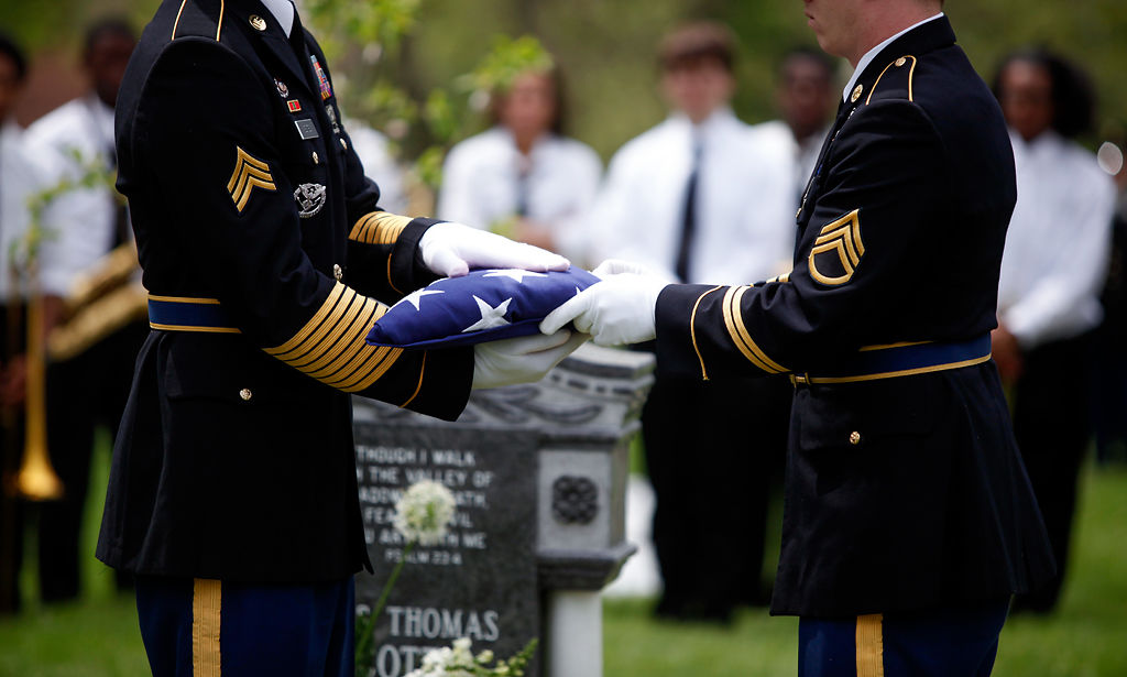 The Missouri Military Honors Unit folds an American flag in front of James T. Scott's headstone