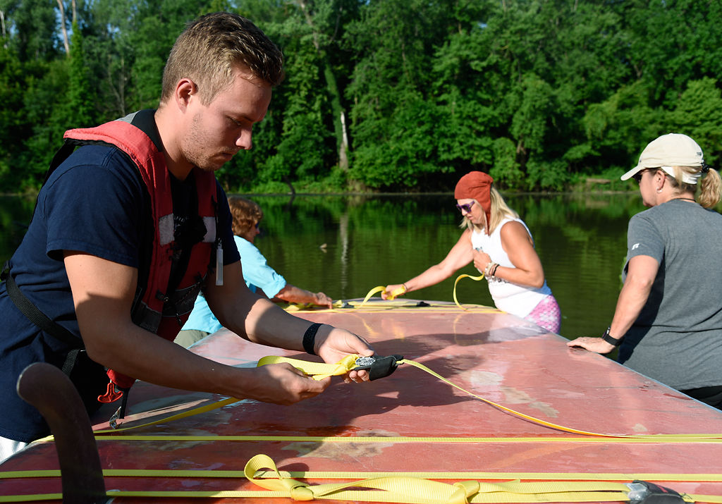 From left, Justin Brooke, Linda LaFontaine, Jessica Kiefer, and Cami Ronchetto unload the six-person paddleboard