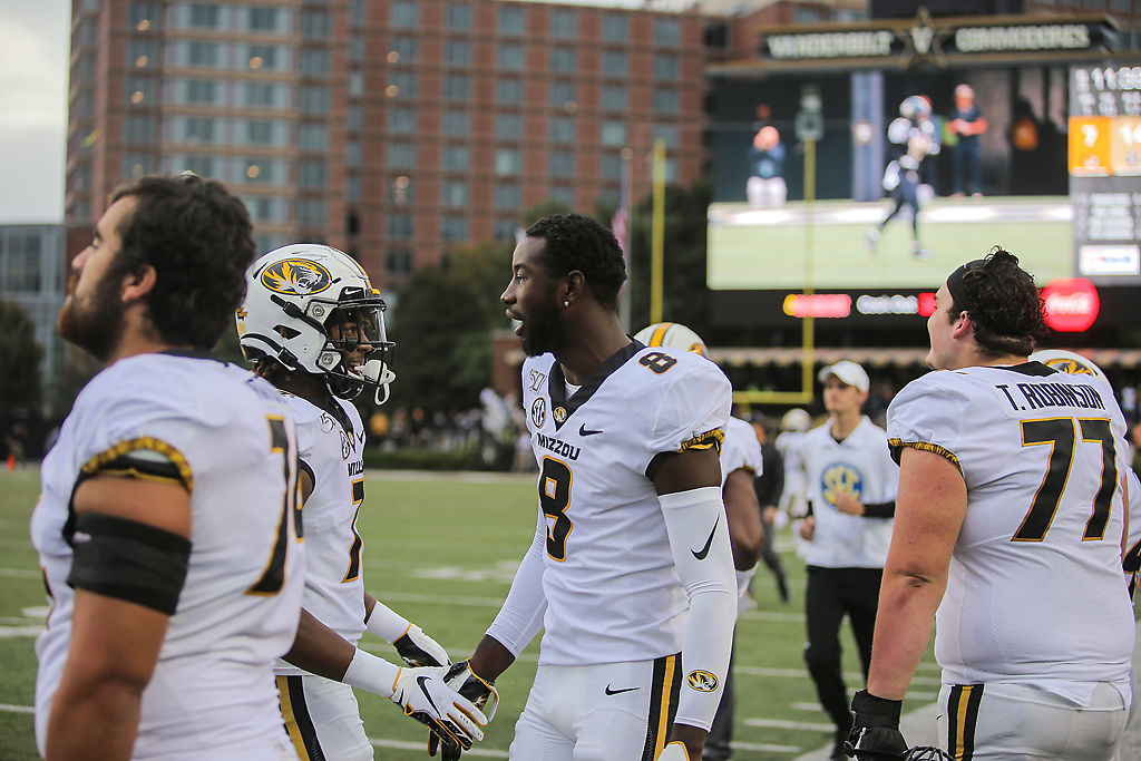 Wide receiver Justin Smith, right, welcomes defensive back Stacy Brown to the sidelines after a defensive stop
