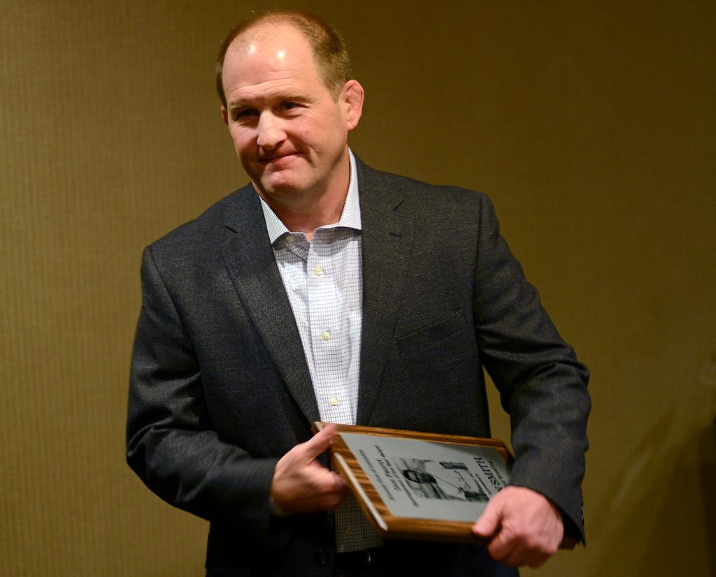 Missouri wrestling coach Brian Smith holds his award