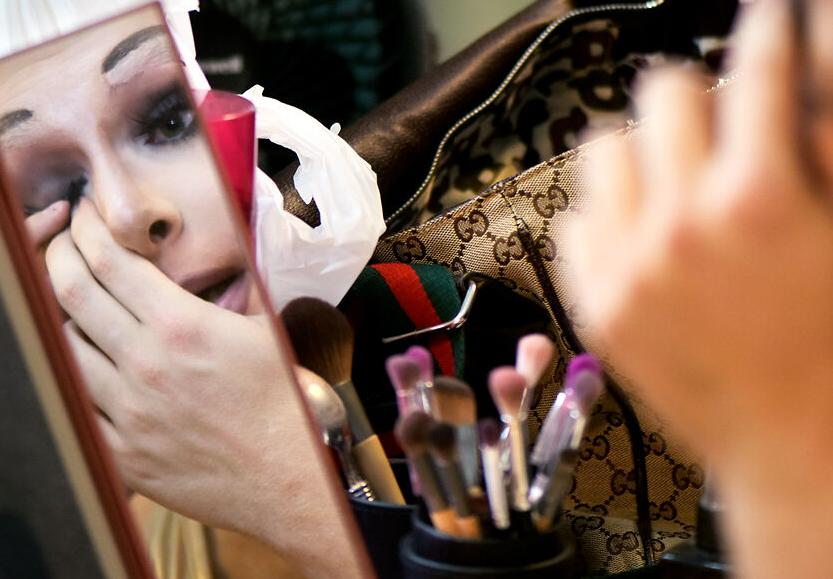 Lady Persona applies her eyelashes before the performance