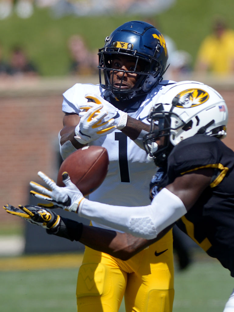 DeMarkus Acy attempts to intercept a pass intended for West Virginia wide receiver T.J. Simmons