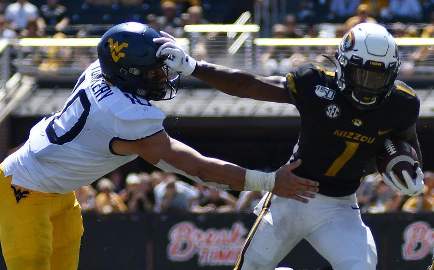 Tyler Badie fends off West Virginia linebacker Dylan Tonkery