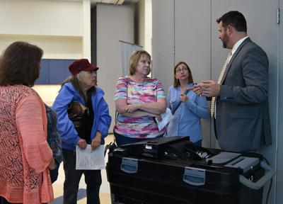 A group of visitors talk with Cory Nibert, right, about the Dominion Voting machines
