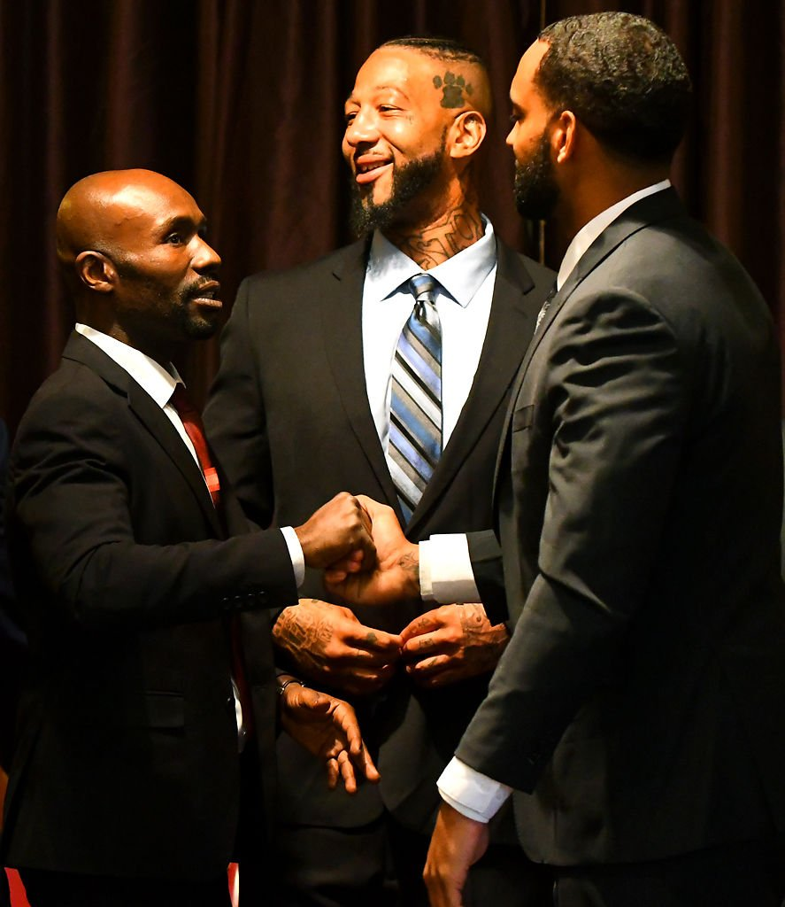 From left, J.C. Dennis, Emory Hayes and Jason Parker shake hands in congratulations after a reentry program graduation