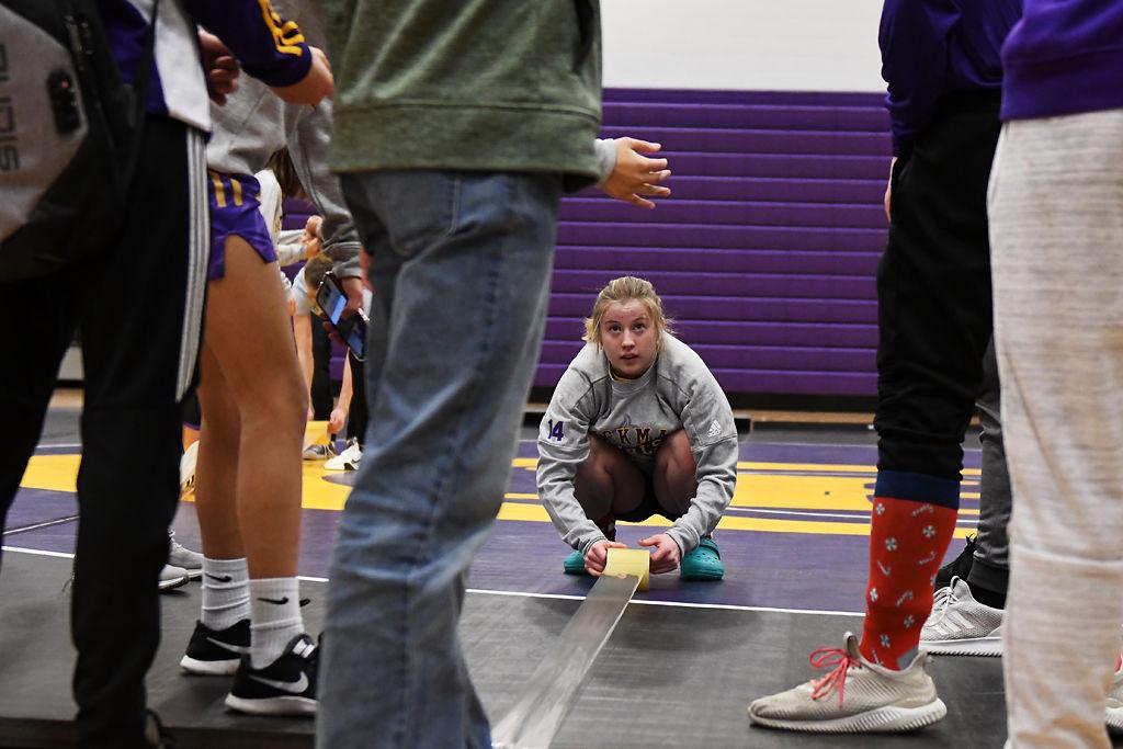 Hickman wrestler Belle Harrell tapes down the mats
