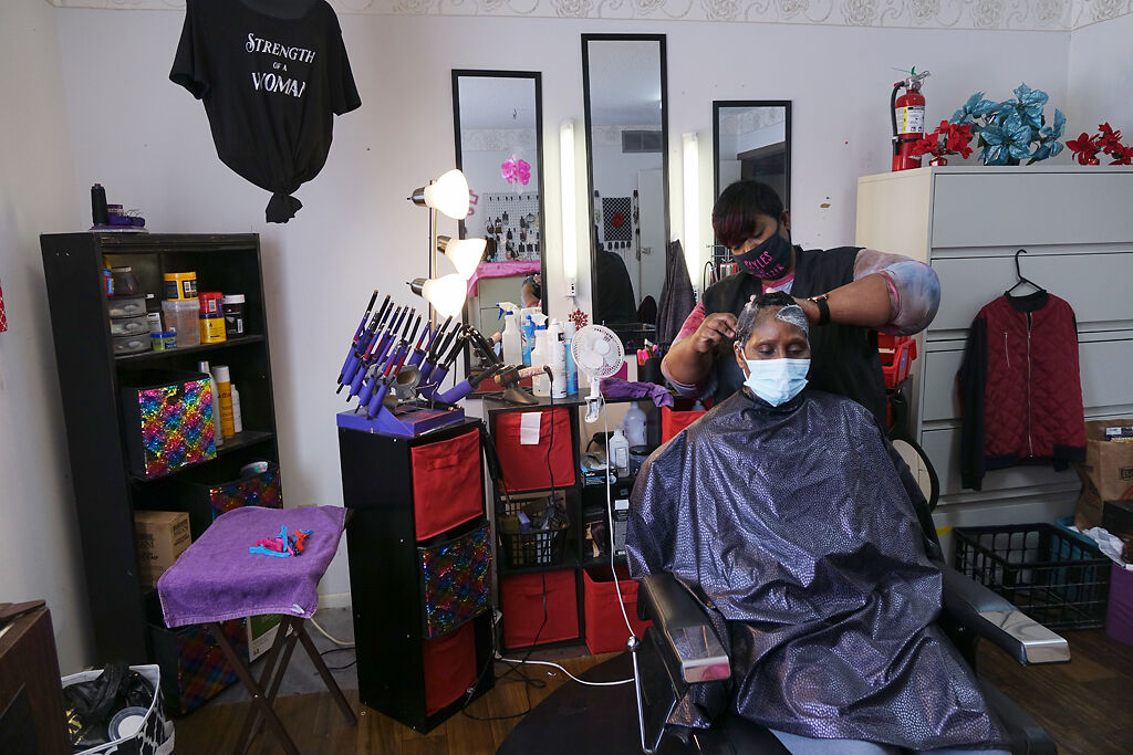 Barbara Prince works in her salon with Theresa Boone