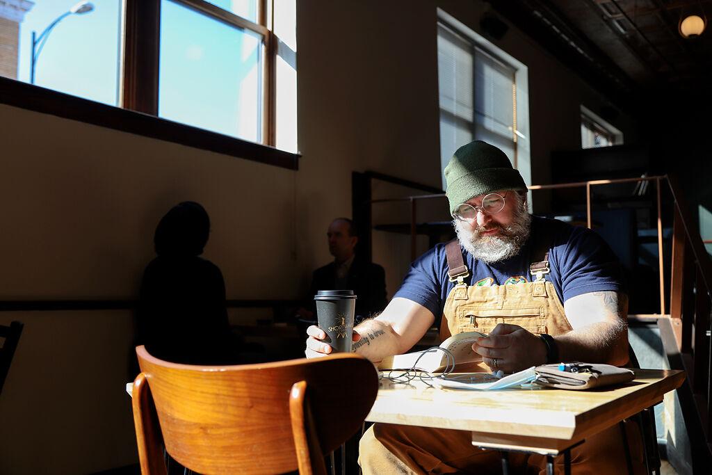 Noah Siela drinks coffee and reads
