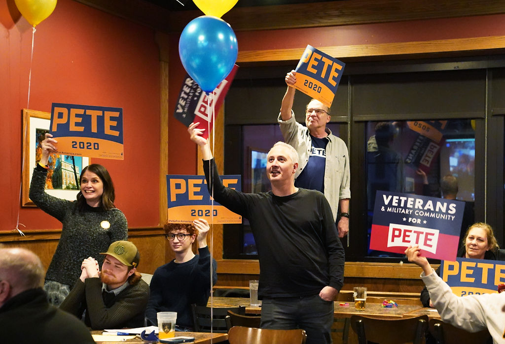 Supporters of Pete Buttigieg hold up campaign signs during their call with other remote watch parties for the candidate