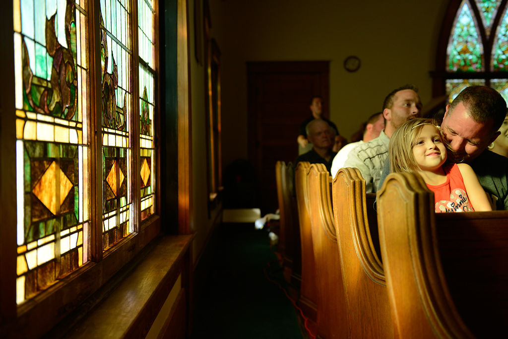 Zailey Hodson smiles as deacon Aaron Duncan talks to her during a hymn