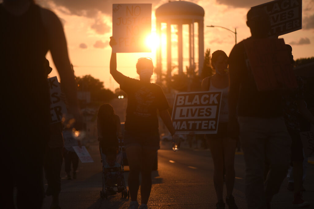 Peoples Defense protesters march up Walnut Street on Monday