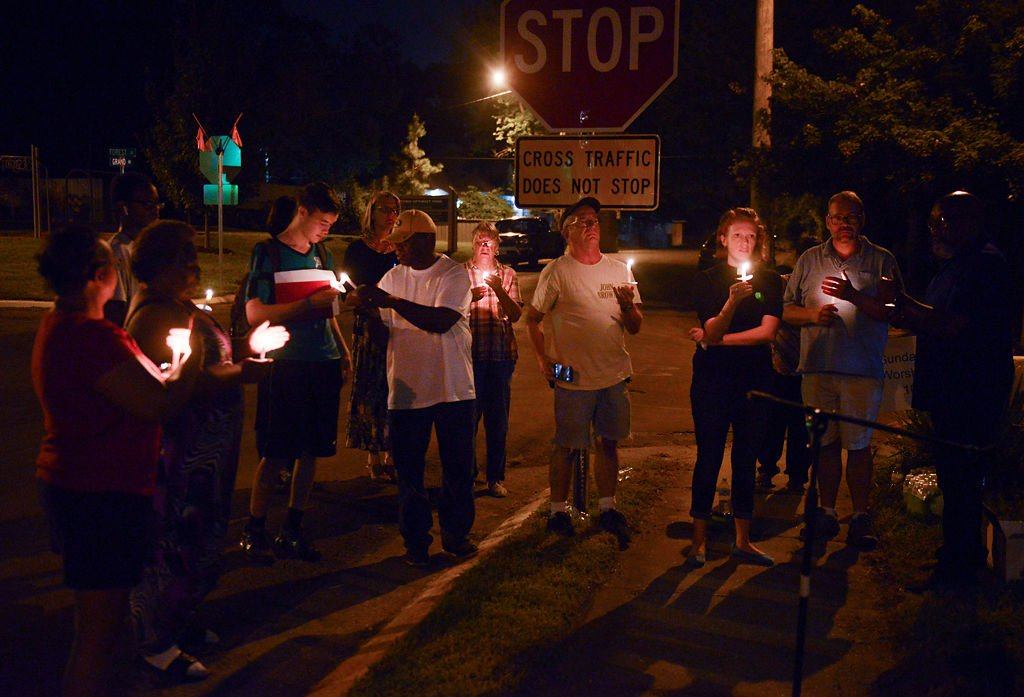 The group of attendees hold candles in front of the stop sign