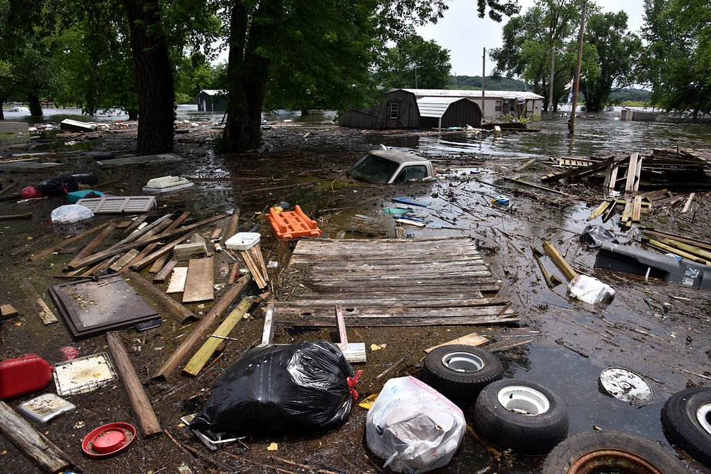 Debris from houses float toward the shore