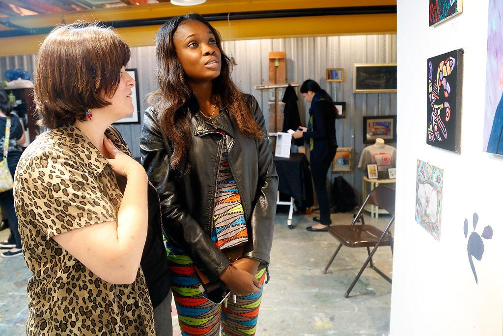Tracie Vangel and Anoucha Mukoko look at artwork