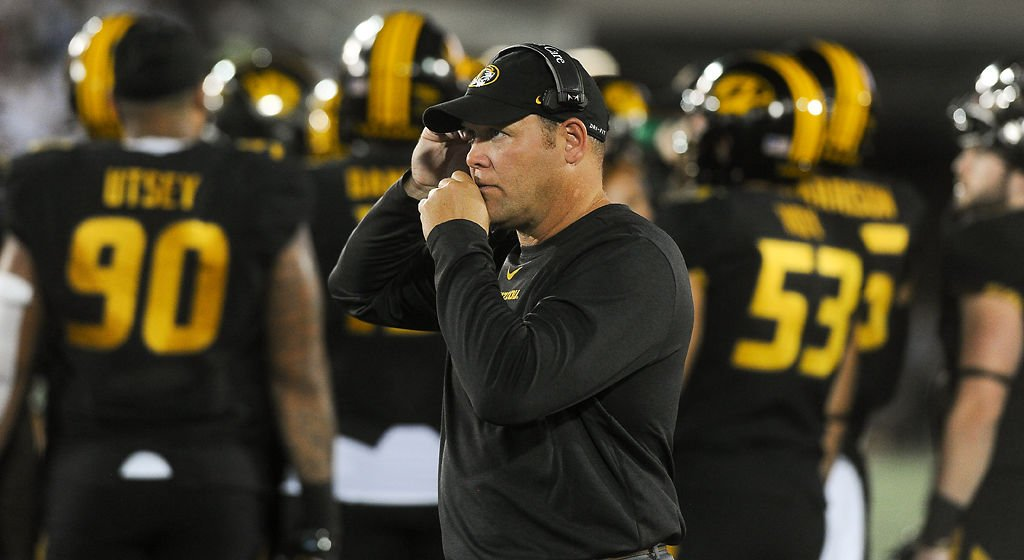 Barry Odom communicates with his coaching staff