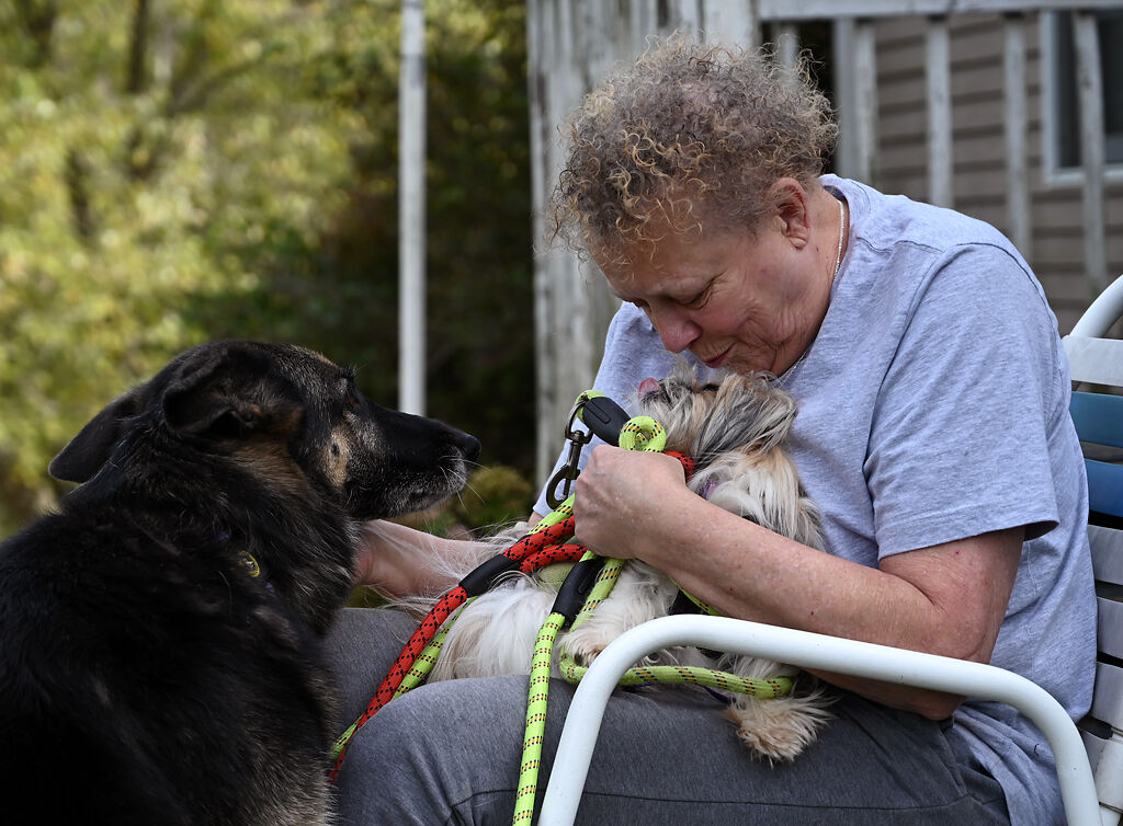 Karen Schams pets Jessie, 7, while receiving kisses from Pookie, 1,