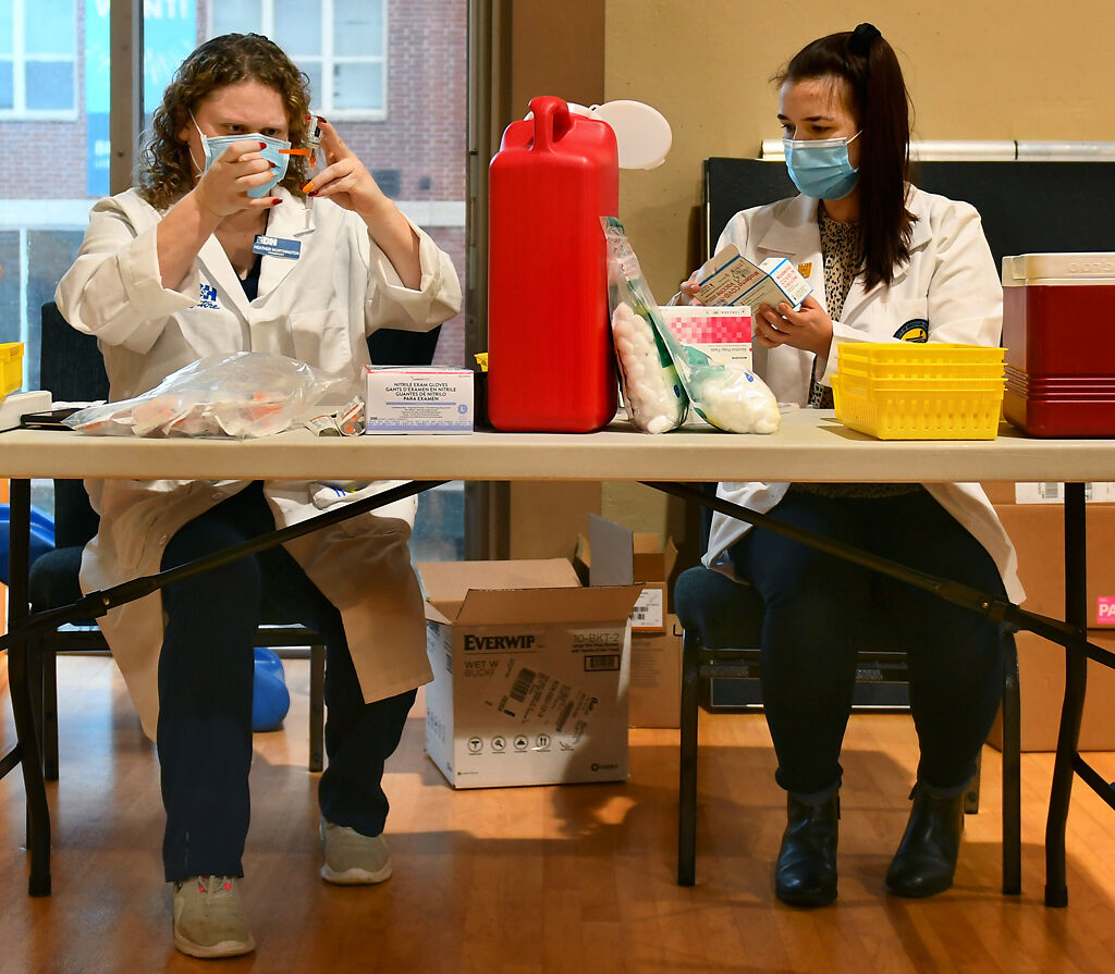 Pharmacist Heather Worthington and UMKC pharmacy student prep vaccines