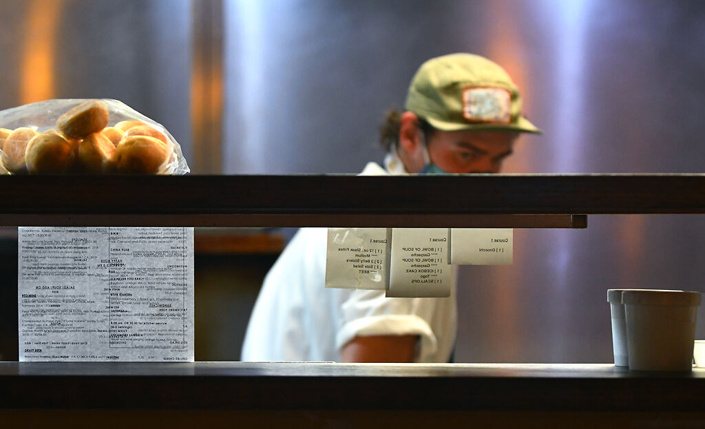 Brian Doss turns to read an order receipt Tuesday in the kitchen at Sycamore Restaurant