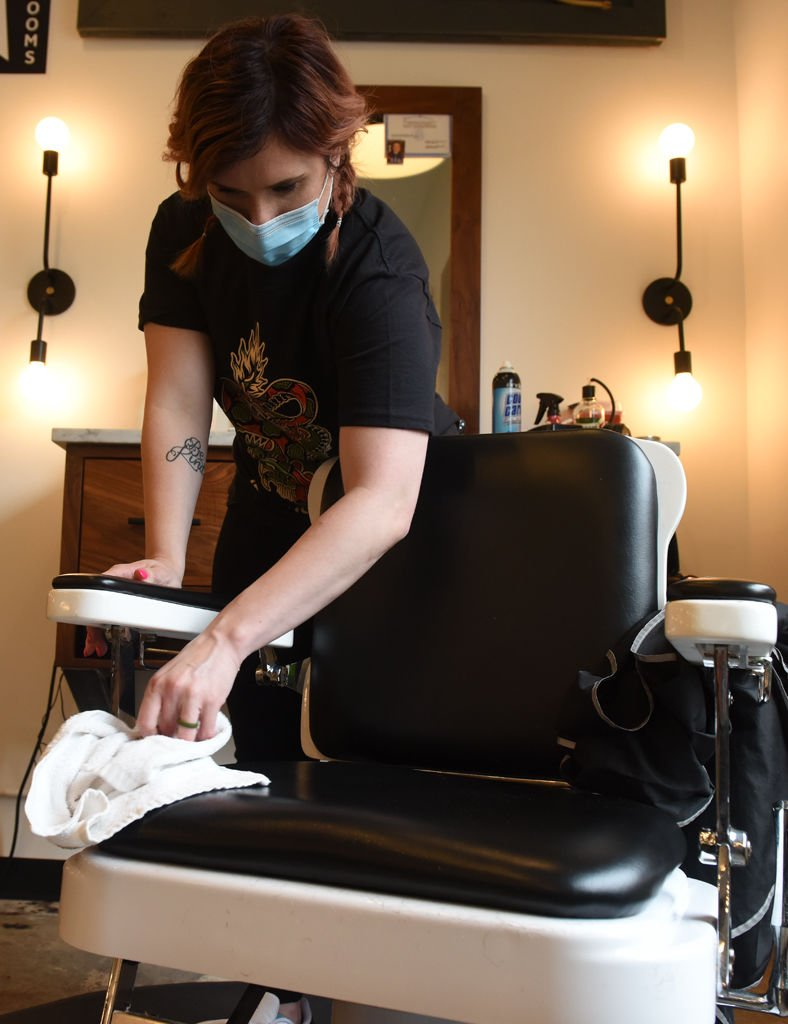 Dani Ledbetter wipes down a barbershop chair