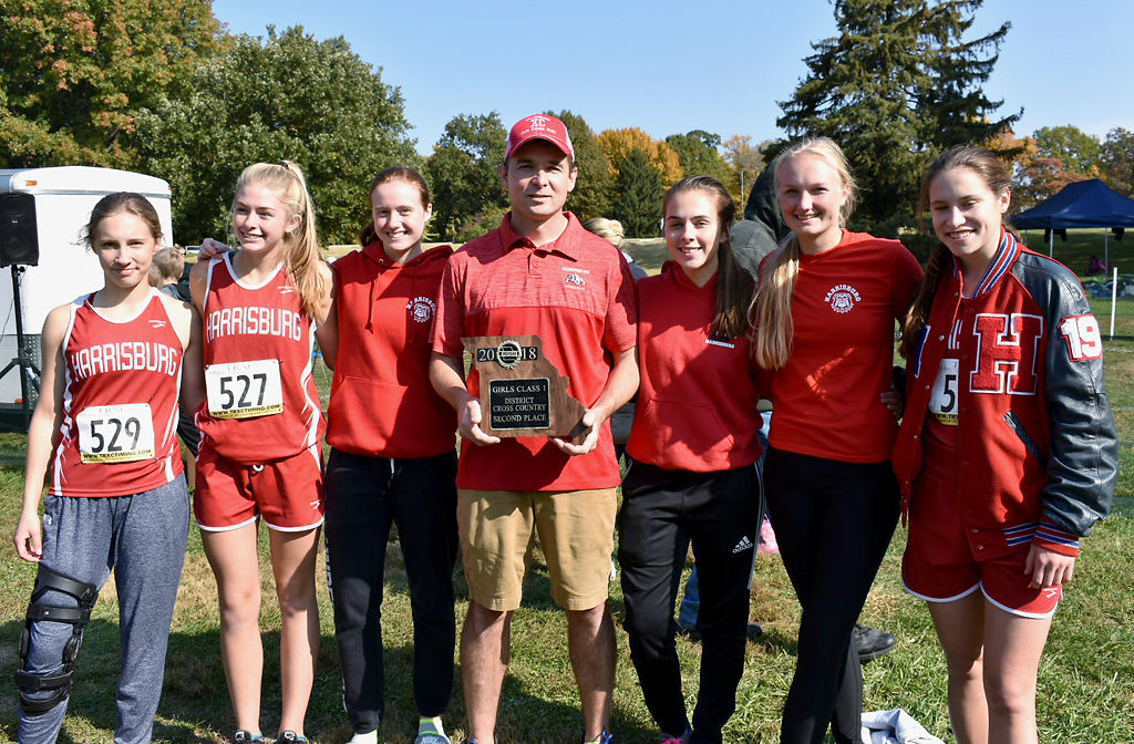 Coach Corey Whitaker stands with the Harrisburg cross country team