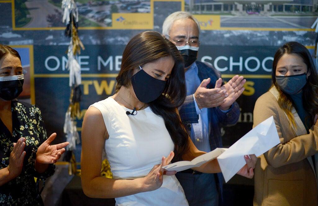 Natalie Rodriguez, center, opens the envelope