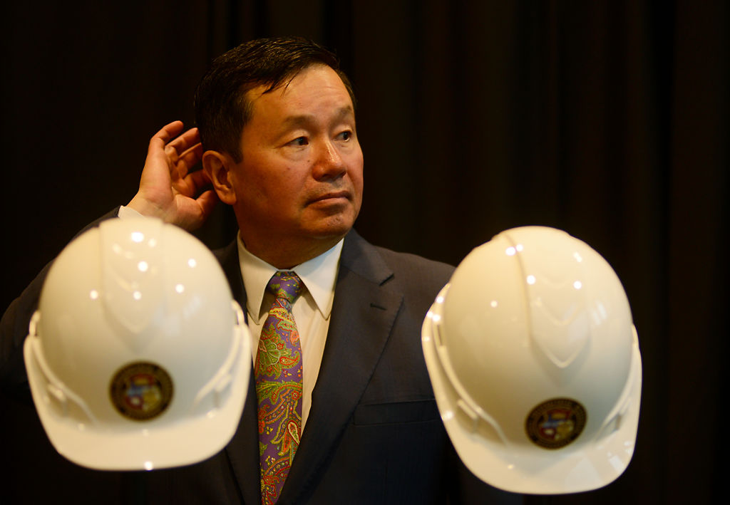 MU System President Mun Choi waits behind the ceremonial hard hats and gold shovels