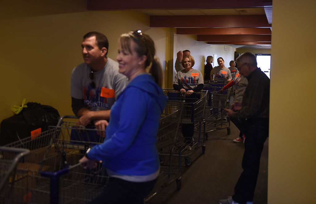 Volunteers line up with carts in the hallway of Woodcrest Church for the 36th annual Holiday Program of the Voluntary Action Center on Thursday