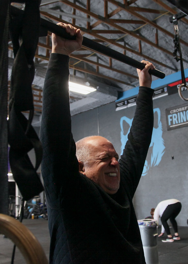 Lance Winkler grasps a pull-up bar during a CrossFit Fringe Vitality class