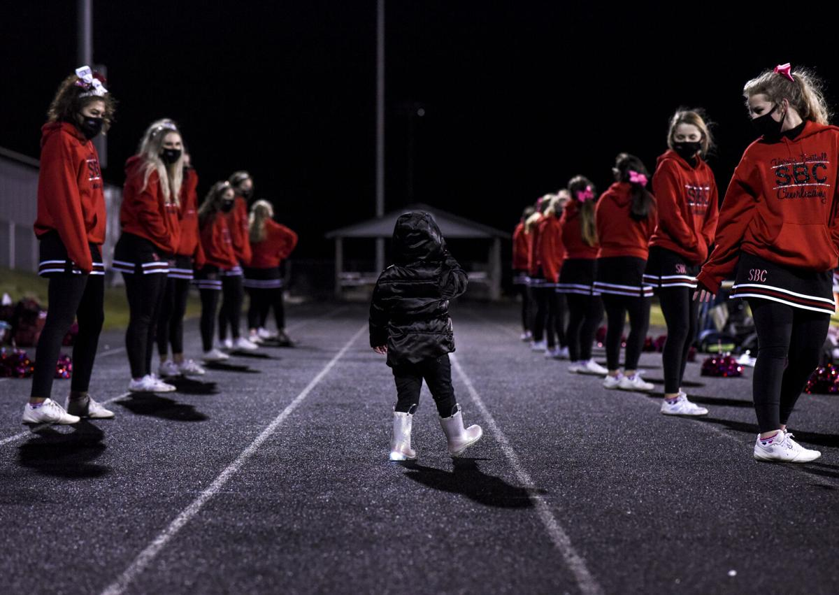 Holly Tracy, 4, waddles through rows of giggling cheerleaders during a Southern Boone High School football game against California High Schoo