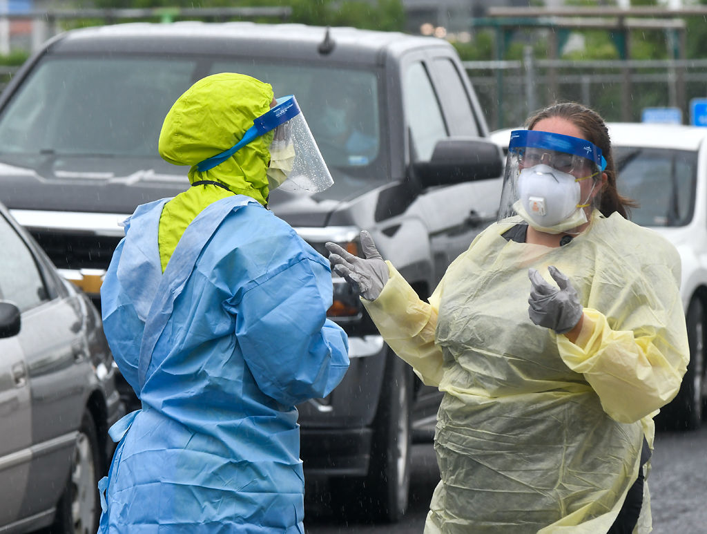 Zorina Pina-Hauan, left, and Crystal Smith talk while dressed in protective equipment