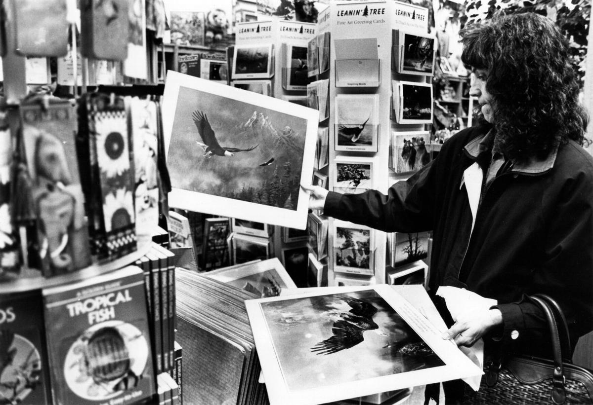 Carolyn Malicoat ponder which Ted Blaylock wall print to buy for a friend while shopping