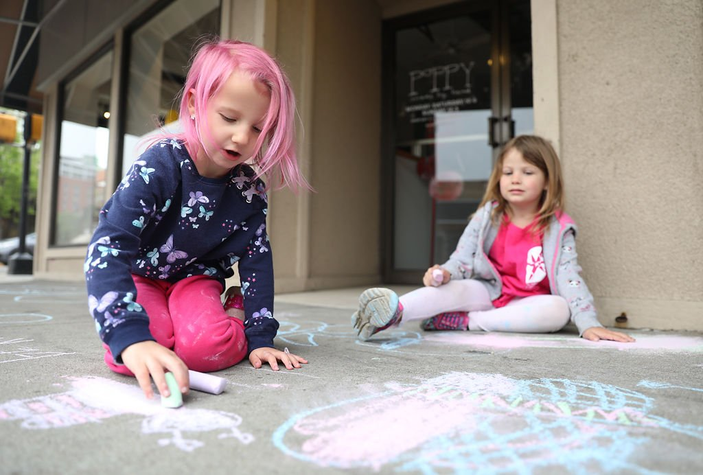 Two children draw butterflies on a sidewalk with chalk