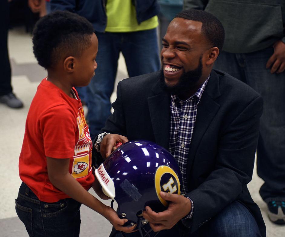Caleb Smith, 6, shows a helmet to the new Hickman football coach, Cedric Alvis (copy)