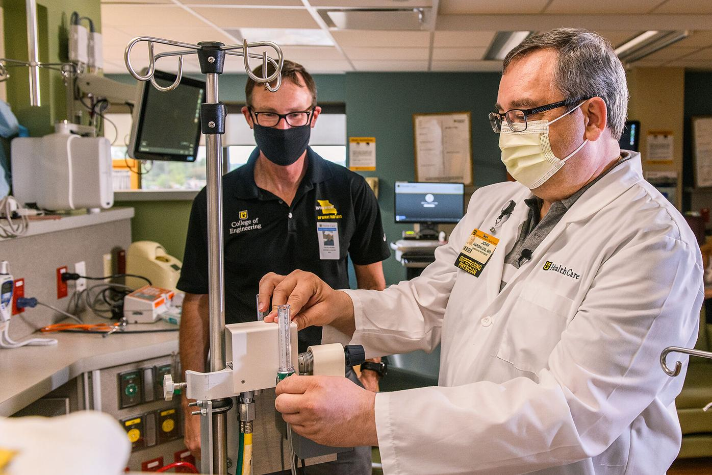 Roger Fales, left, and John Pardalos set up the oxygen control device