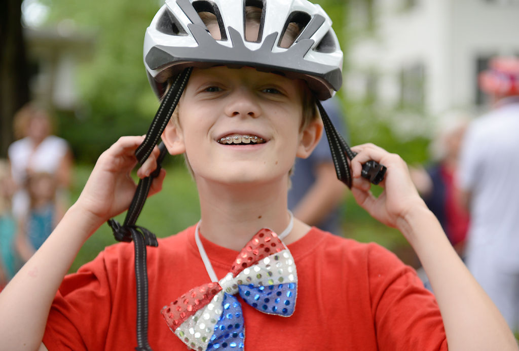 Harvey Munter, 10, puts on his helmet before the Park Hill Fourth of July parade begins