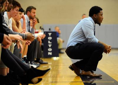 Jeremy Osborne kneels in front of the Tolton bench