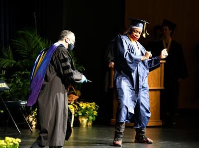 Dennis Darks dances across the stage to receive his diploma