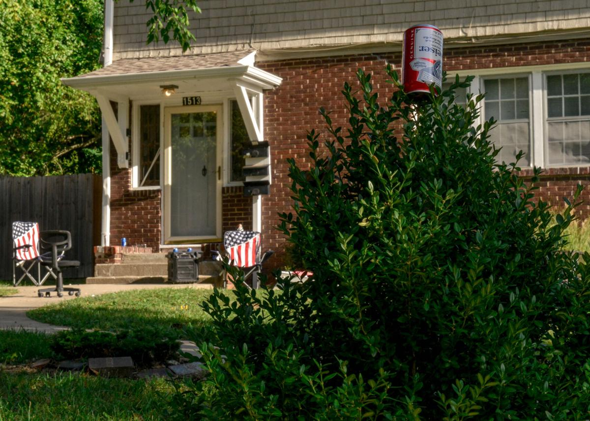 An empty beer can adorns the front bushes of an East Campus house