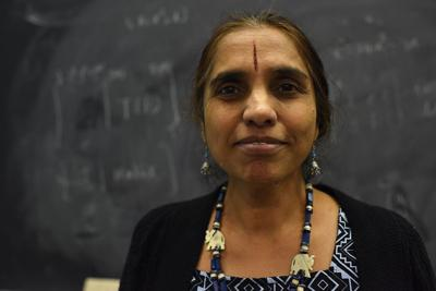 Hema Srinivasan stands in front of her chalkboard