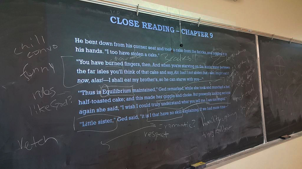A passage written by Ursula K. Le Guin is annotated on a blackboard