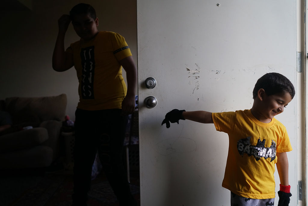 Mohamed Baqer, 4, walks out the back door of his family's apartment