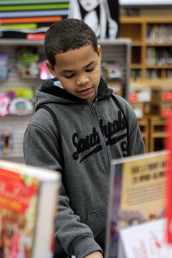 Joshua Gibson, 12, looks through cook books