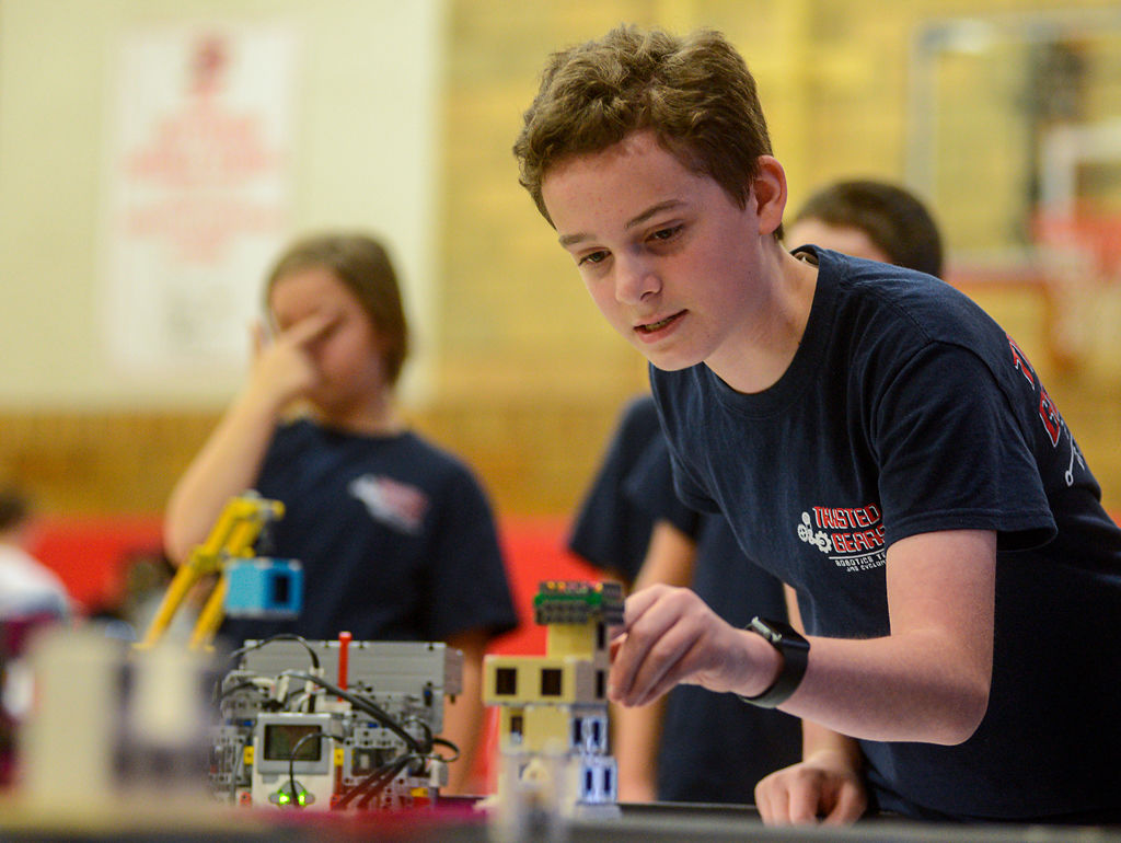 Gabe Palmer, 12, prepares his team's LEGO robot before the start of a competition